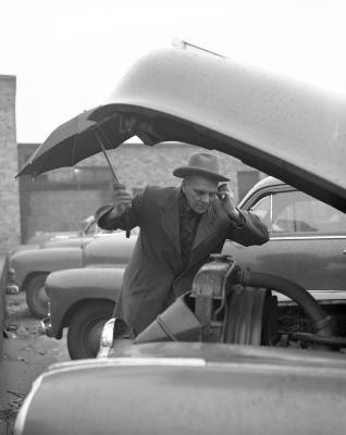 Anderson, Louie, looking under hood of car