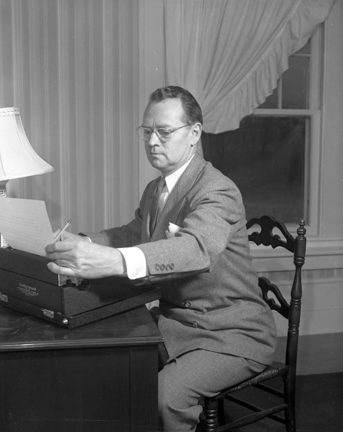 Backus, William at typewriter