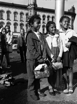 Children waiting to board bus at Monument Square